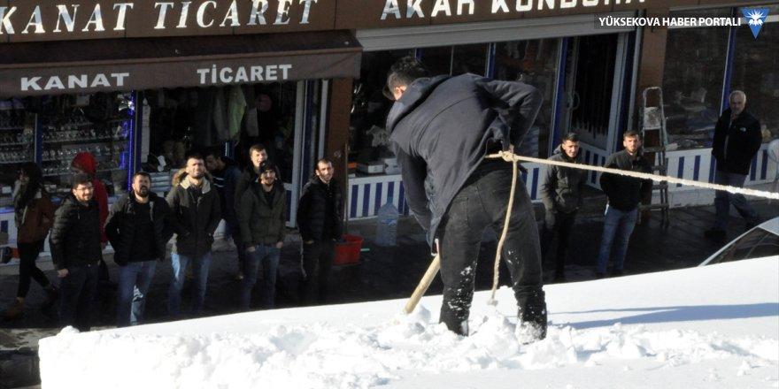 Çukurca: Karla kaplı çatıda güvenliklerini iple sağladılar
